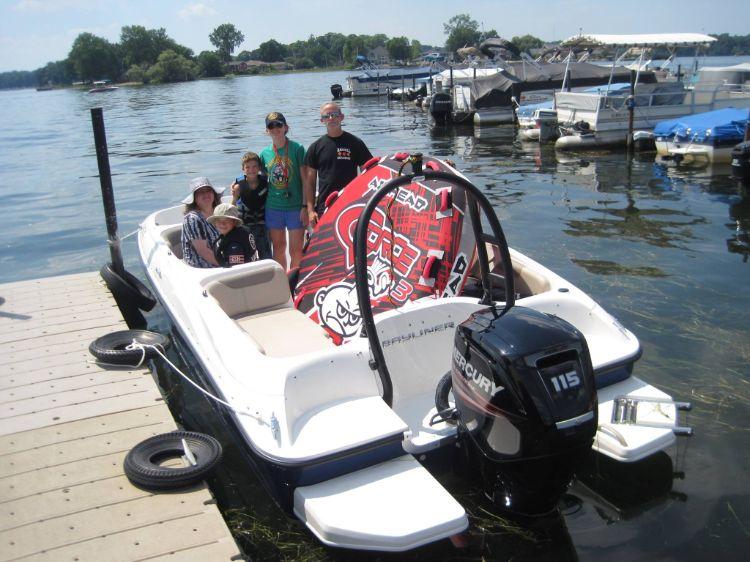 Family renting ski boat with tube