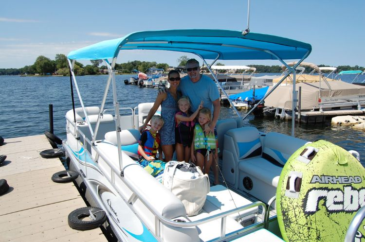 Family with three girls taking out pontoon with tube